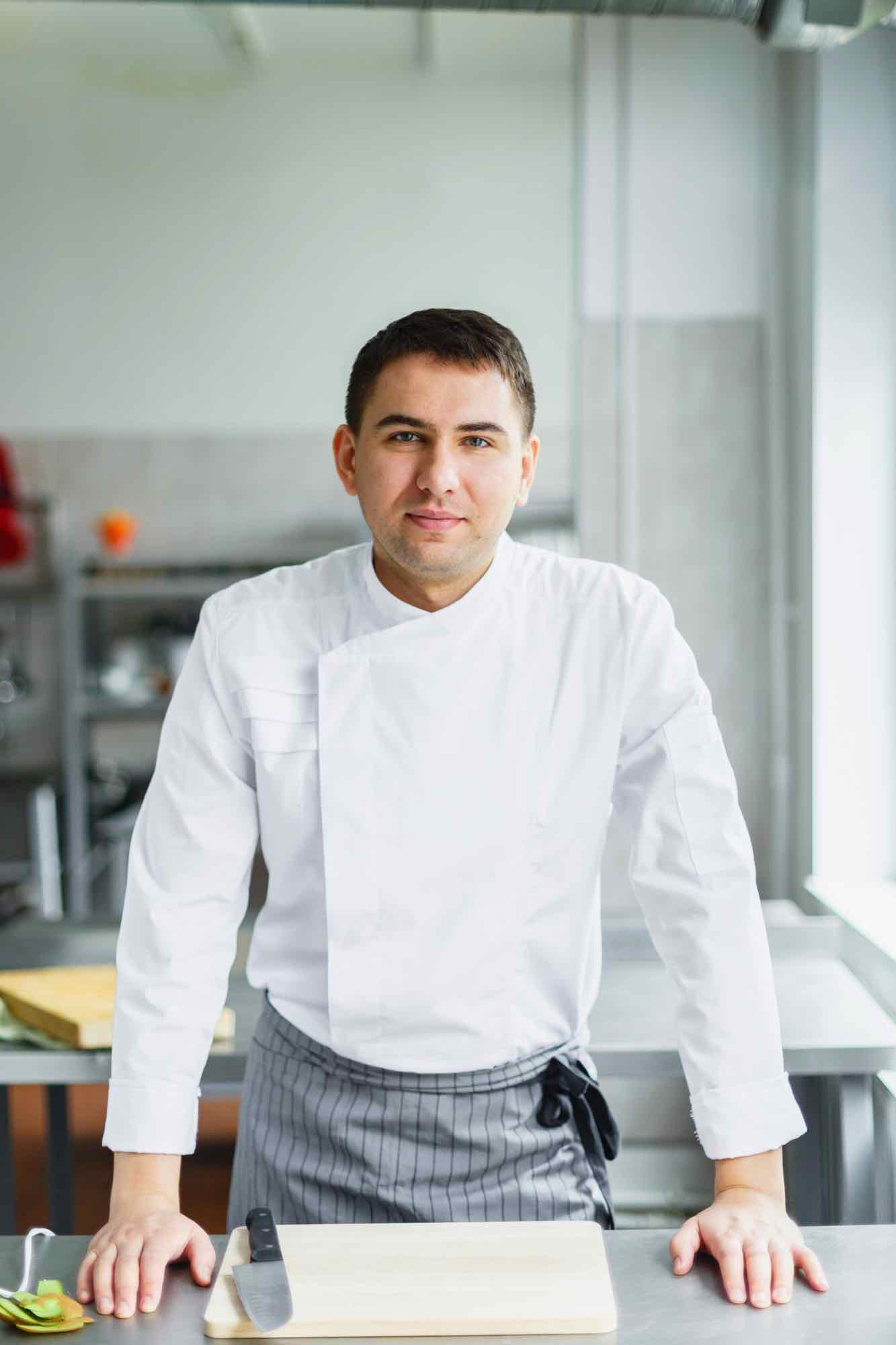 young-smiling-male-chef-posing-PDEM7CR.jpg