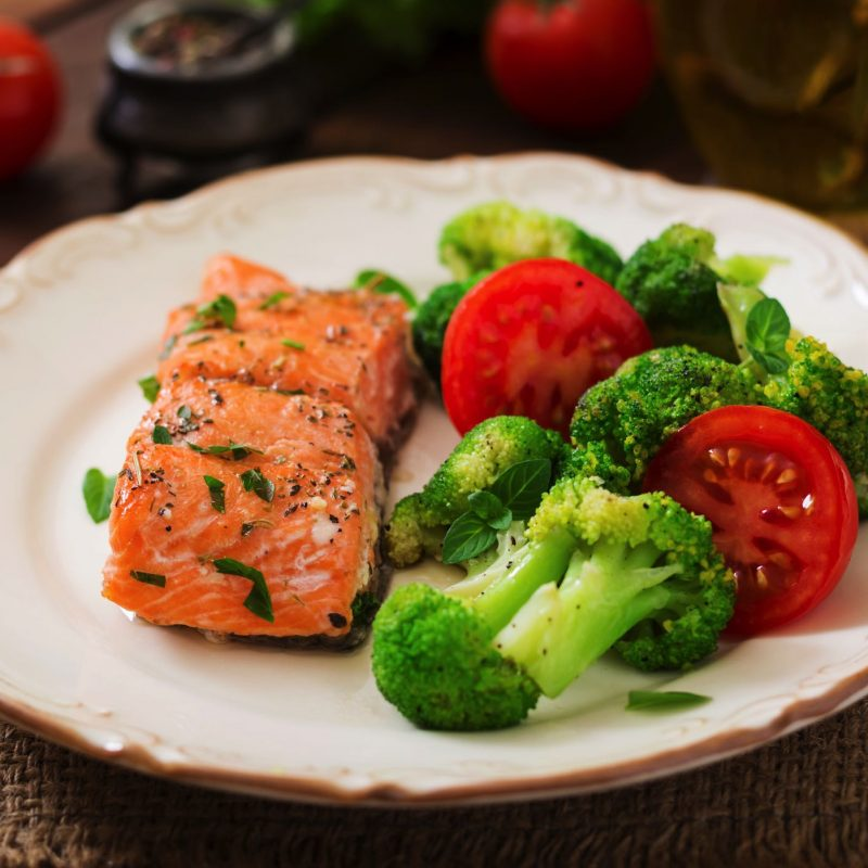 baked-fish-salmon-garnished-with-broccoli-and-toma-PBKGZRK.jpg