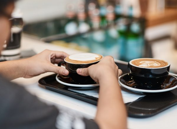 Professional waiter serving a cup of coffee